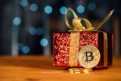 Bitcoin BTC cryptocurrency and Christmas gift box. BTC golden coin as symbol of electronic virtual money for web banking and international network payment royalty free stock photography