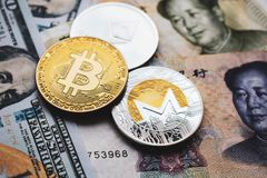 Bitcoin, Ethereum, Monero coins on Chinese Yuan and US dollars banknotes royalty free stock image