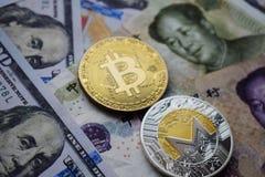 Bitcoin BTC och Monero XMR mynt på kinesiska Yuan och US dollarsedlar royaltyfria bilder