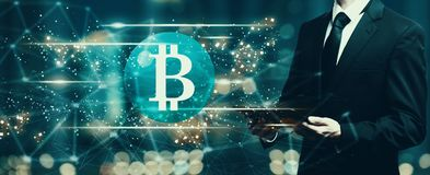 Bitcoin with businessman holding a tablet Royalty Free Stock Photo