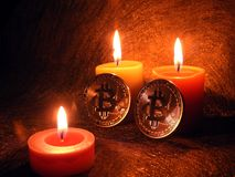Bitcoins and three candlelight`s. Bitcoin in candlelight`s on golden background royalty free stock photography