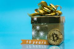 Bitcoin celebrating birthday, coin with birthday golden present behind it and 10 years sign, with blue copy space. Closeup photo of Bitcoin cryptocurrency royalty free stock image
