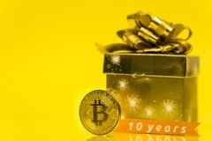 Bitcoin celebrating birthday, coin with birthday golden present behind it and 10 years sign, with yellow copy space. Closeup photo of Bitcoin cryptocurrency stock images