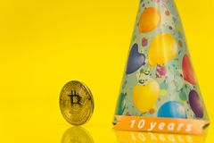 Bitcoin celebrating birthday - 10 years, coin with birthday hat behind it and 10 years sign, with yellow copy space. Closeup photo of Bitcoin cryptocurrency royalty free stock images