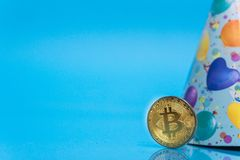 Bitcoin celebrating 10 year anniversary, coin with birthday hat behind it, with blue copy space. Closeup photo of Bitcoin cryptocurrency celebrating birthday royalty free stock photos