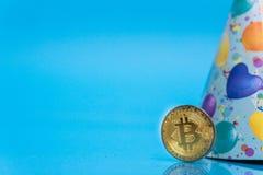 Bitcoin che celebra un anniversario di 10 anni, moneta con il cappello di compleanno dietro, con lo spazio blu della copia fotografie stock libere da diritti