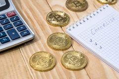 Bitcoin with checklist on a notepad with pen. And calculator royalty free stock photo