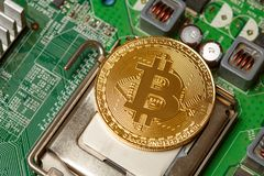 Golden Bitcoin Cryptocurrency on computer circuit board. Macro shot. Bitcoin is on the chip as a processor. Mining cryptocurrency. The concept of technologies of Stock Photography