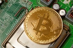 Golden Bitcoin Cryptocurrency on computer circuit board. Macro shot. Bitcoin is on the chip as a processor. Mining cryptocurrency. The concept of technologies of Stock Images