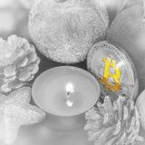 Bitcoin among Christmas decorations and a candle. royalty free stock photo