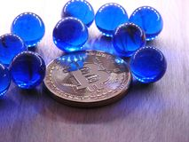 Bitcoin with blue glass marbles. Royalty Free Stock Images