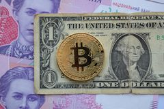 Bitcoin coin on american, and ukrainian banknotes royalty free stock photos