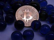 Bitcoin coin between blue glass marbles. Bitcoinc Coin between blue glass marbles background Royalty Free Stock Photos