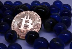 Bitcoin coin between blue glass marbles. Bitcoinc Coin between blue glass marbles background Royalty Free Stock Photography