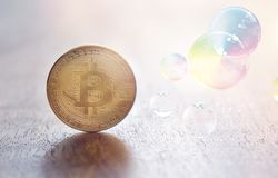 Bitcoin coin and bursting soap bubble stock images
