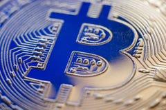 Bitcoin coin currency closeup on blue light. Bitcoin currency DOF on blue glass background. Gold metal curency symbol macro photo closeup stock photo