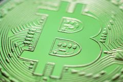 Bitcoin coin currency closeup on green light. Bitcoin currency DOF on blue glass background. Gold metal curency symbol macro photo closeup royalty free stock photo