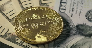Bitcoin coin on the dollar banknotes spinning on a black background stock footage