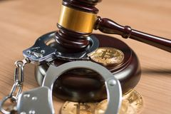 Bitcoin coin and gavel on a desk. Bitcoin regulation. BTC cryptocurrency coin and judge gavel on a desk. Banned currency or law enforcement concept stock image
