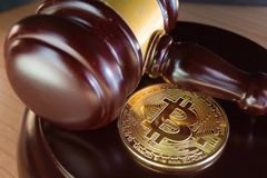 Bitcoin coin and gavel on a desk. Bitcoin regulation. BTC cryptocurrency coin and judge gavel on a desk. Banned currency or law enforcement concept stock photo