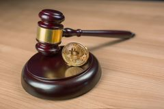 Bitcoin coin and gavel on a desk. Bitcoin regulation. BTC cryptocurrency coin and judge gavel on a desk. Banned currency or law enforcement concept royalty free stock images