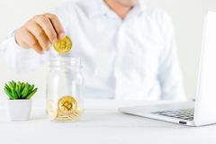 Bitcoin coin golden coin in the glass jar on wooden table ,Man h Royalty Free Stock Photography