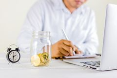 Bitcoin coin golden coin in the glass jar on wooden table ,Man r Royalty Free Stock Image