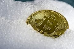 Bitcoin coin on ice or snow. Bitcoin coin on ice, concept image for cooled curse of bitcoin crypto currency Stock Images
