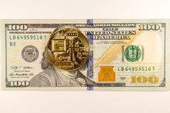 Bitcoin coin lies on 100 dollars bankton on a white background stock photography