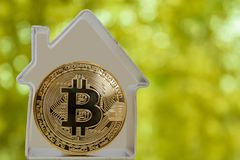 Bitcoin coin in a metal house. On a green background. Rent or buy a house for bitcoins Stock Photography