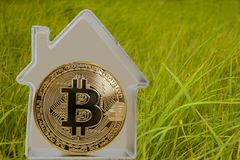Bitcoin coin in a metal house. On a green grass background. Rent or buy a house for bitcoins Royalty Free Stock Images