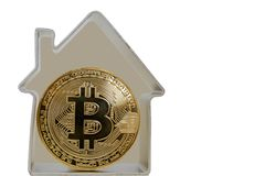 Bitcoin coin in a metal house. On a white background. Rent or buy a house for bitcoins Stock Photography