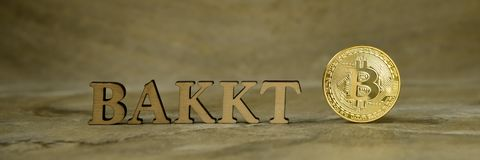 Bitcoin coin and next to wooden with BAKKT stock photo