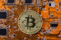 Bitcoin coin on orange computer circuit board. Motherboard Stock Image