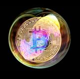 Bitcoin coin in a soap bubble. Concept of instability of the crypto currency. Bitcoin coin in a soap bubble. Concept of instability of the crypto currency over Royalty Free Stock Photo