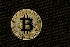 Bitcoin coin standing on a black background with computer langua. Ge numbers 0 and 1 in the background Stock Photography