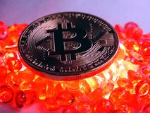 Bitcoin coin on top of red hot burning  beats. Bitcoinc Coin on top of red hot colored burning beats background Stock Photography