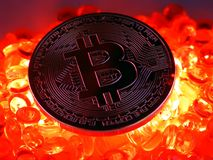 Bitcoin coin on top of red hot burning beats. Bitcoinc Coin on top of red hot colored burning beats background royalty free stock photo