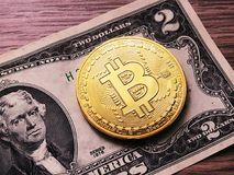 Bitcoin coin & two dollars bill Stock Images