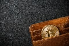 Bitcoin coin in wallet on black background. Copy space Royalty Free Stock Image