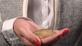 Bitcoin coin in woman's hands