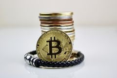 Bitcoin coins and black bracelet Royalty Free Stock Photography