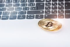 Bitcoin coins on a keyboard of white laptop. Computer. Investment situation. New virtual currency. Most valuable cryptocurrency Stock Photography