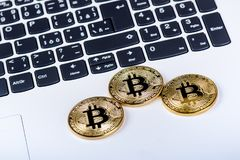 Bitcoin coins on a keyboard of white laptop. Computer. Investment situation. New virtual currency. Most valuable cryptocurrency Stock Photos