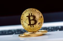 Bitcoin coins on a keyboard of white laptop. Computer. Investment situation. New virtual currency. Most valuable cryptocurrency Royalty Free Stock Image