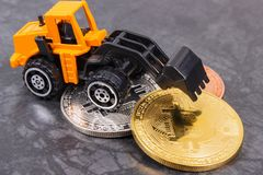 Bitcoin coins with miniature excavator, concept of mining cryptocurrency royalty free stock image