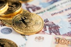 A close up image of bitcoins with Russian rubles banknotes. Bitcoin coins new virtual money on Russian banknotes. A close up image of bitcoins with Russian stock images