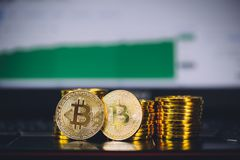 Bitcoin coins pile and two bit coins sitting in front with market spiking and turning green graph chart digital background. Concept of Bitcoin and virtual Stock Photos