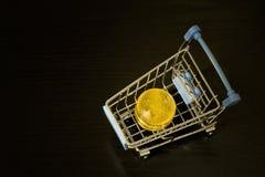 Bitcoin coins in shopping cart. Black background Stock Photos