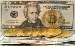 Bitcoin coins on United States US twenty dollar bill $20. Virtual cryptocurrency money Bitcoin golden coins on United States US twenty dollar bill $20 with the stock images